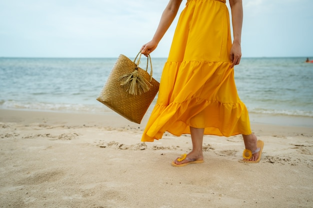 Ноги женщины в желтом платье гуляют на морском пляже с сумкой Premium Фотографии