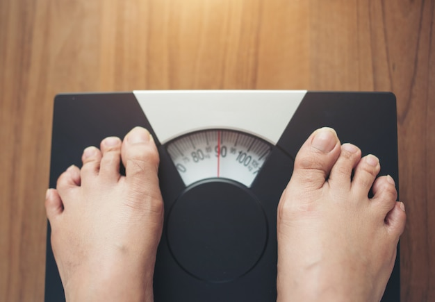 Женщина ноги, стоя на вес шкалы на деревянном фоне Бесплатные Фотографии