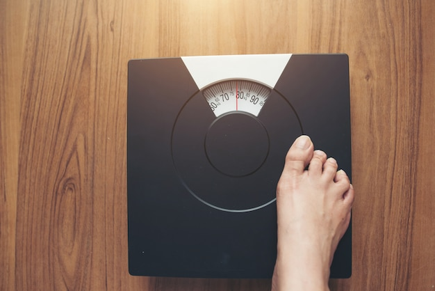 Woman feet standing on weight scale on wooden background Free Photo