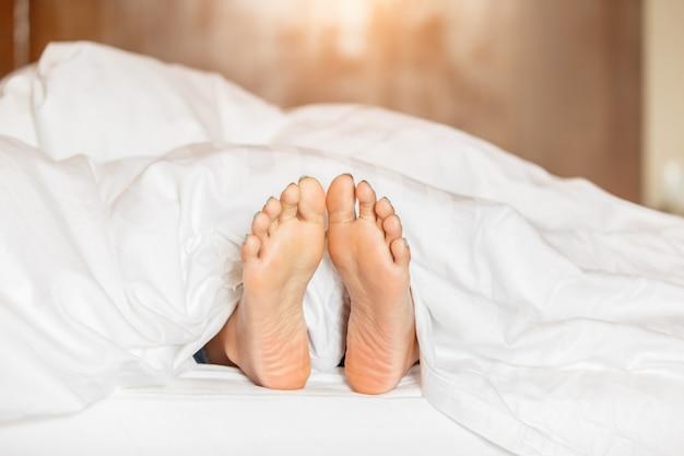Woman feet under white blanket side view Premium Photo