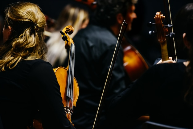 Woman fiddler during a concert, background in black. Premium Photo