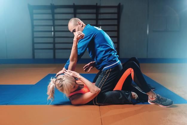 Женщина борется с мужчиной, техника самообороны Premium Фотографии