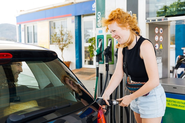 Woman filling up car and laughing with man in it Free Photo