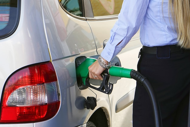 Woman fills petrol into her car at a gas station closeup. woman hand holding a fuel pump at a station. Premium Photo