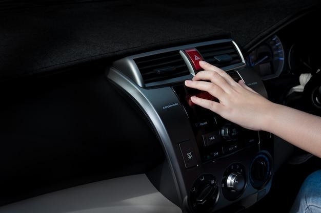 車の中で車の非常灯ボタンを押すと女性の指 Premium写真