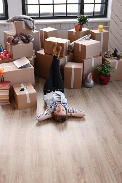 La donna ha finito con i pacchi di carico ed è sdraiata sul pavimento Foto Gratuite