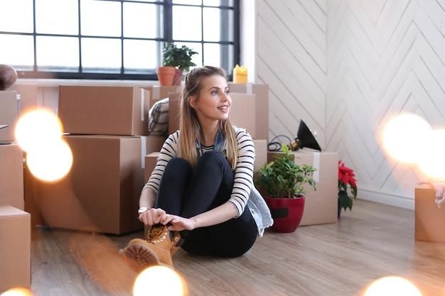 La donna ha finito con i pacchi di carico ed è seduta accanto alle scatole sul pavimento Foto Gratuite