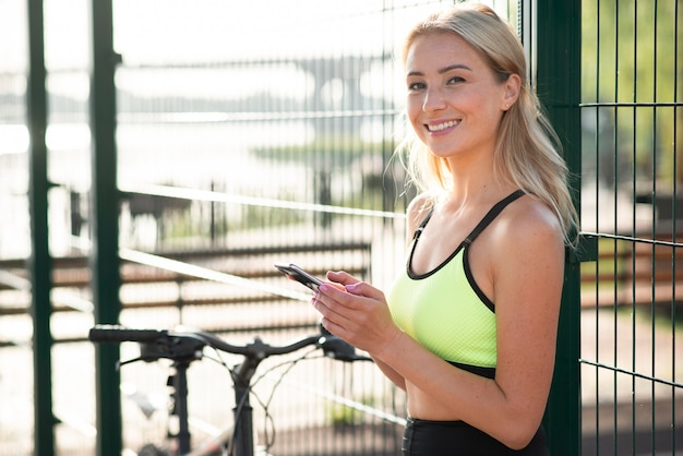 Woman in fitness clothes using her  mobile phone Free Photo