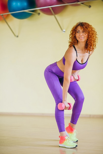 Woman fitness trainer with dumbbells Free Photo
