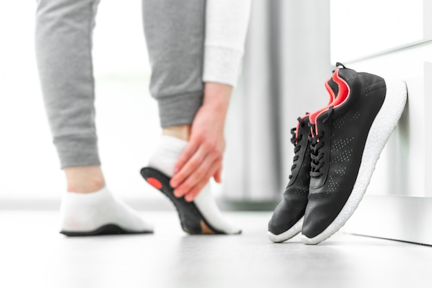 Woman fitting orthopedic insoles. treatment and prevention of flat feet and foot diseases. foot care, feet comfort. health care. wearing sports comfortable shoes Premium Photo
