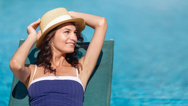 Woman fixing hat laying on sunbed Free Photo
