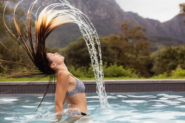 Woman flipping her hair in swimming pool Free Photo
