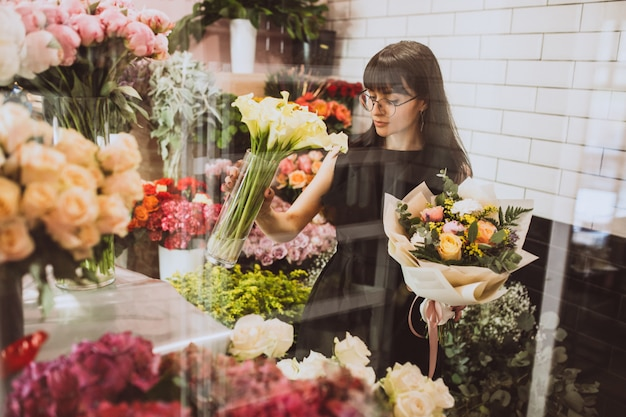 Woman florist at her own floral shop taking care of flowers Free Photo