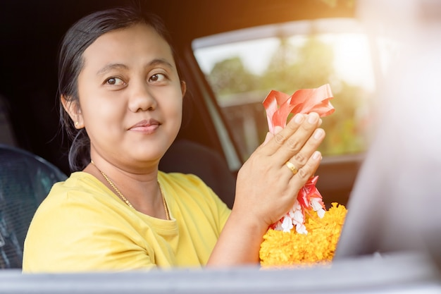 Woman flower garland in hand and praying in the new car for lucky Premium Photo