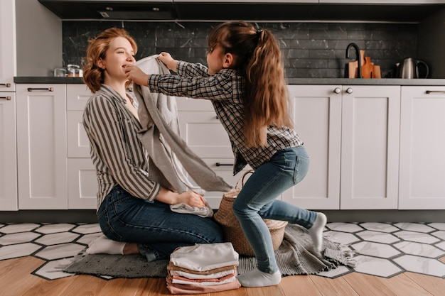 Woman folds clothes from laundry basket while her daughter plays in kitchen. Free Photo