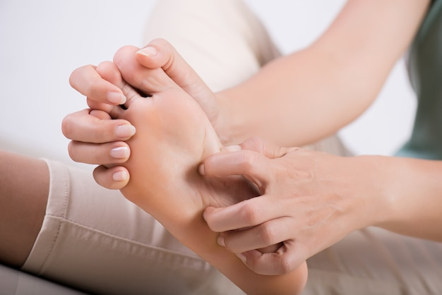 Woman foot scratch the itch by hand at home. healthcare and medical concept. Premium Photo