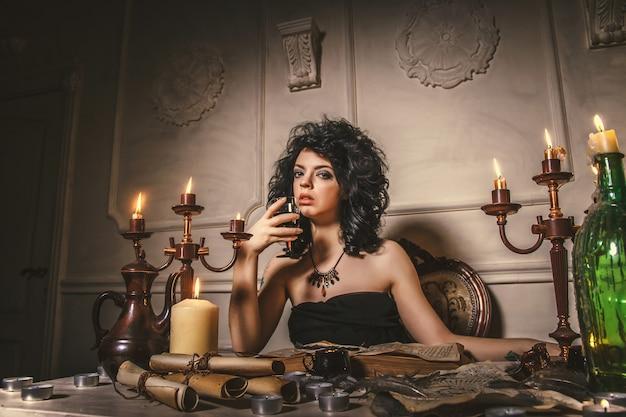 Женщина-гадалка угадывает судьбу ночи за столом со свечами. волшебная сказка хэллоуина, мистика, девочка вызывает духов. черная магия Premium Фотографии