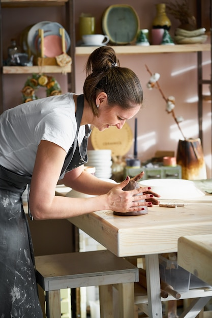 Woman freelance, business, hobby. woman making ceramic pottery on table in studio Premium Photo