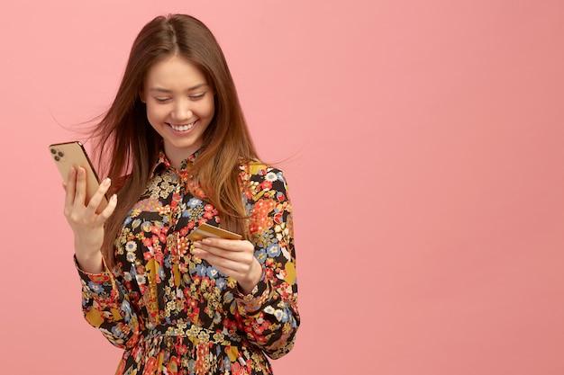 여자는 은행 서비스, 온라인 구매, 학생 제안과 함께 신용 카드를 사용하여 휴대 전화를 손에 보유하고 있습니다. 프리미엄 사진