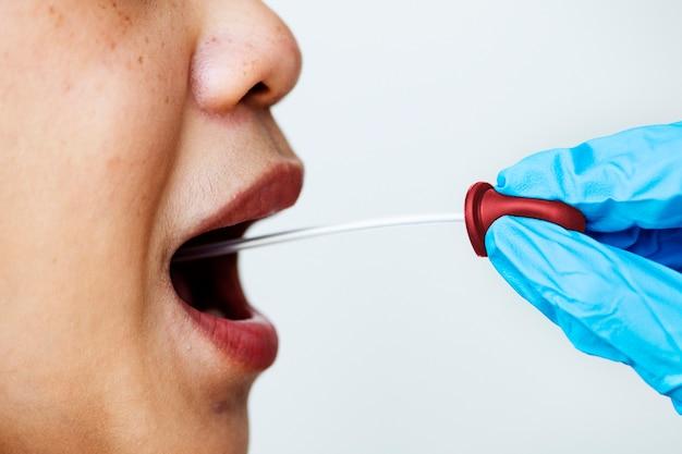 Женщине берут мазок изо рта для проверки на коронавирус Бесплатные Фотографии