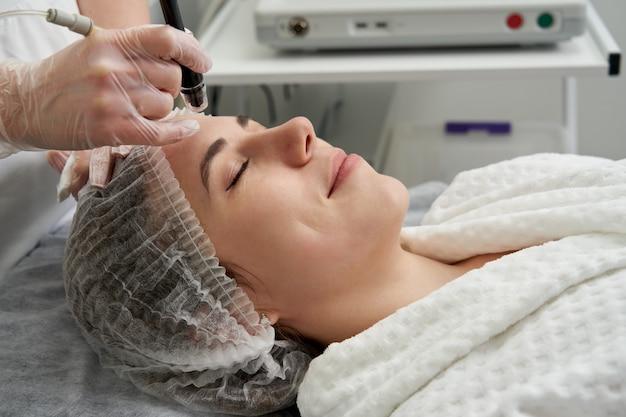 Женщина получает лечение пилинга лица hydro microdermabrasion в косметической спа-клинике красоты. гидра Premium Фотографии