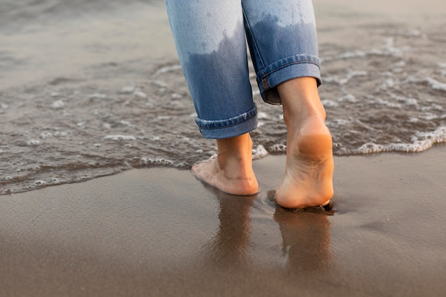Woman getting her feet in the water at the beach Free Photo