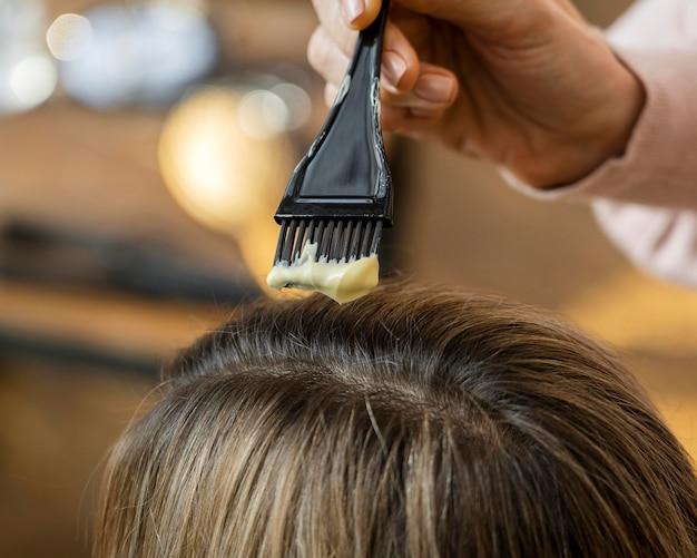 미용사에 의해 집에서 그녀의 머리를 염색하는 여자 무료 사진