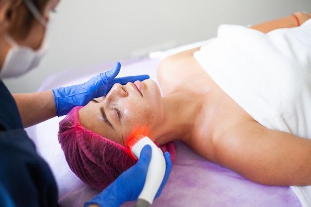 Woman getting lpg hardware massage at clinic. Premium Photo