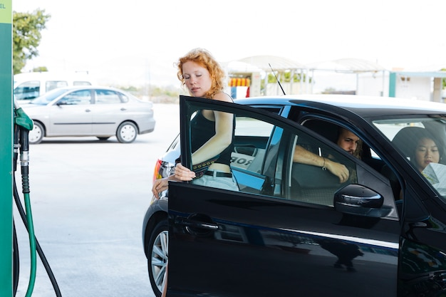 Woman getting out of car at gas station Free Photo