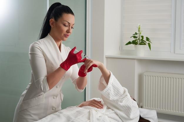 Женщина получает инъекции омолаживающего наполнителя в руке. косметолог, вводя наполнитель в кожу рук Premium Фотографии