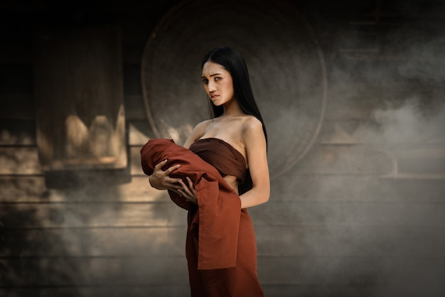 Woman ghost drama and carrying her baby ghost standing on old thai house Premium Photo