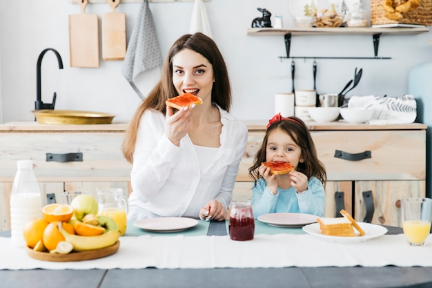 Woman and girl having breakfast at the kitchen Free Photo