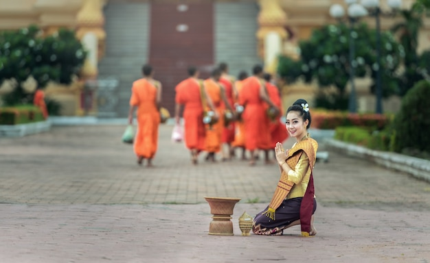 Woman give food offerings to buddhist monks Premium Photo