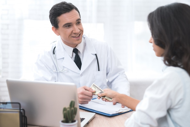 A woman gives money to a doctor in his office. Premium Photo