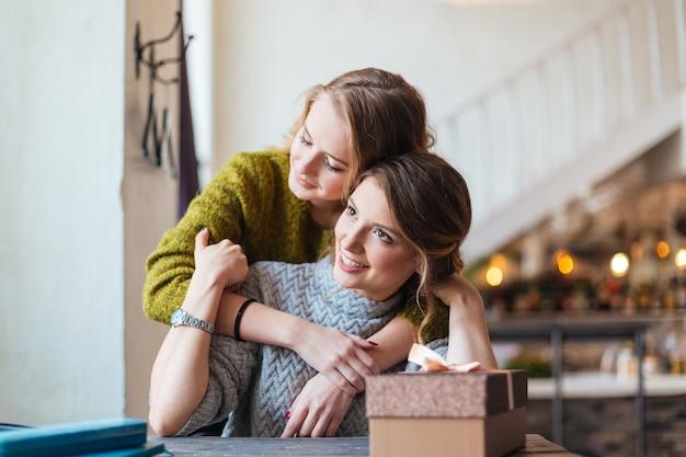카페에서 그녀의 여자 친구에 게 선물 상자를주는 여자 프리미엄 사진