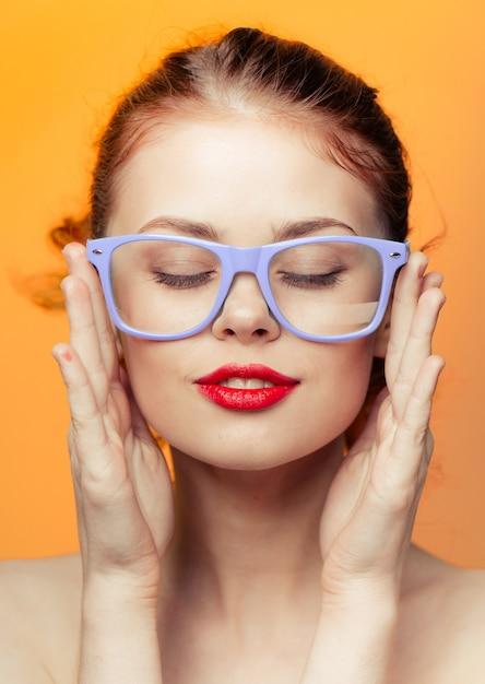 女性メガネ明るい黄色オレンジ色の背景 Premium写真
