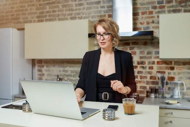 A woman in glasses works remotely on a laptop in her kitchen. a girl gesticulating discusses with her colleagues on an online business briefing at home. . Premium Photo