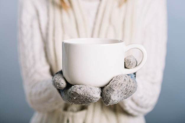 Woman in gloves holding cup Free Photo