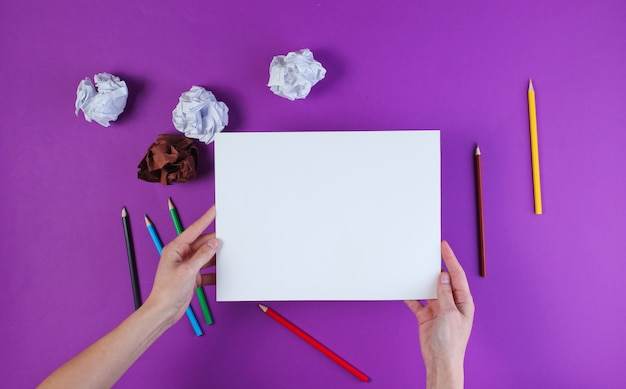 Woman going to draw with colored pencils on a purple surface with crumpled paper balls. Premium Photo