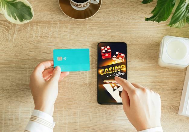 居間からオンラインカジノをプレイし、クレジットカードを持って支払う女性。 Premium写真