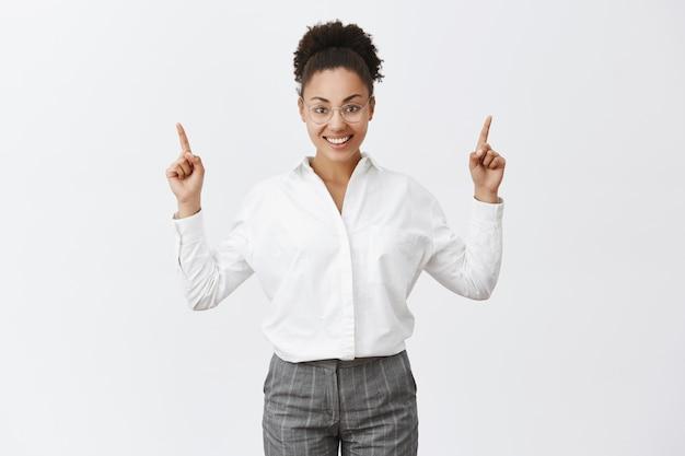 キャリアのはしごを上がる女性。魅力的な成功した、幸せな実業家、暗い肌、人差し指を引き上げ、上向きに、灰色の壁に広く笑みを浮かべて 無料写真