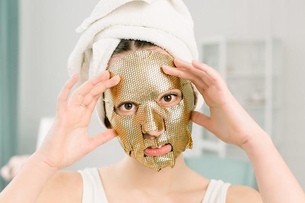 女性ゴールドシートマスク。カメラ目線の黄金の肌の化粧品で頭に白いタオルで美しい若い女性。美容スキンケアと治療 Premium写真
