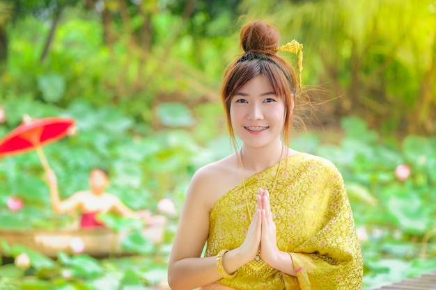 The woman in the golden thai dress is good morning in the lotus garden. Premium Photo