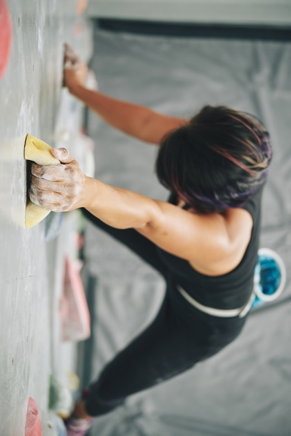 Woman grabbing boulder on climbing wall Free Photo