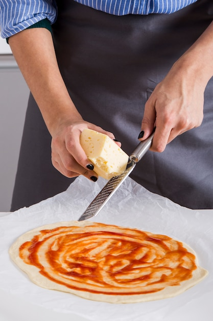 Woman grating the cheese over the homemade pizza bread over the parchment Free Photo