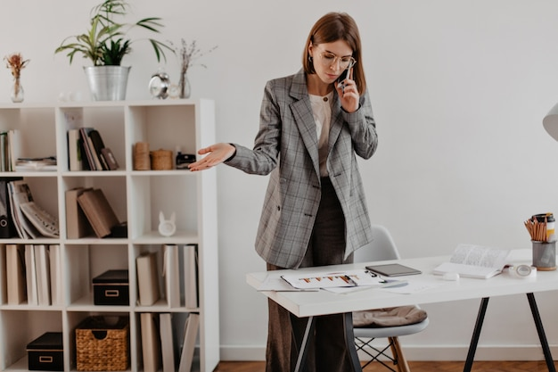 Donna in abito grigio, parlando al telefono con i partner commerciali. ritratto di donna adulta guardando il grafico. Foto Gratuite