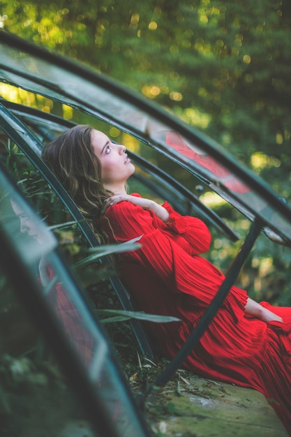 Woman in a green house looking away Free Photo