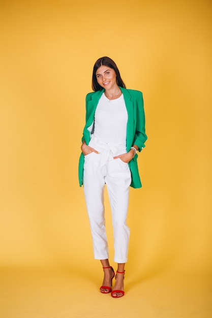 Woman in green jacket in studio on yellow background Free Photo