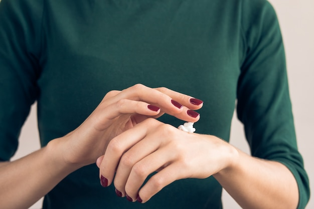 Woman in a green t-shirt and a maroon manicure applying hand cream Premium Photo