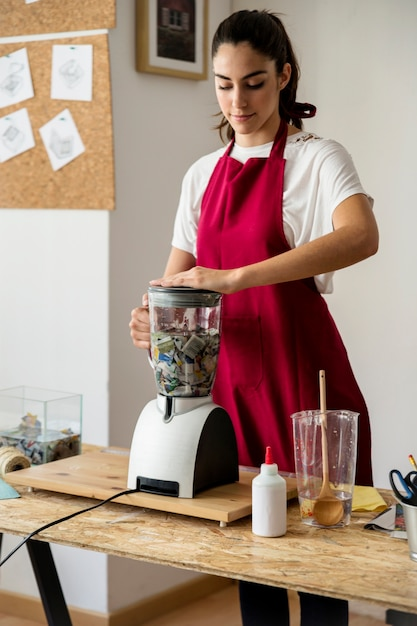 Woman grinding pieces of paper in mixer grinder Free Photo